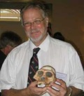 """Dr. Francis THACKERAY Dr. Francis Thackeray at the time Director, Transvaal Museum, South Africa, at the World Heritage of Human Origins Conference, Mildura, April 2007. He is now Director, Insitute of Human Evolution, University of Witwatersrand. He is holding a replica of """"Mrs. Ples"""" from The Cradle of Humankind World Heritage Site, South Africa. It is a specimen of Australopithecus africanus."""